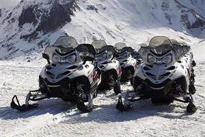 The snowmobiles all lined up and ready to go
