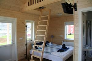 A double bed and a stair to the sleeping loft
