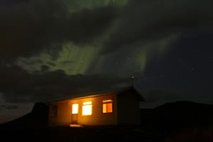 Northern lights dancing on the sky above the Sunset Cottage at Fossatún