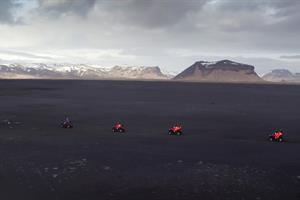 Drive an ATV on a black sand field