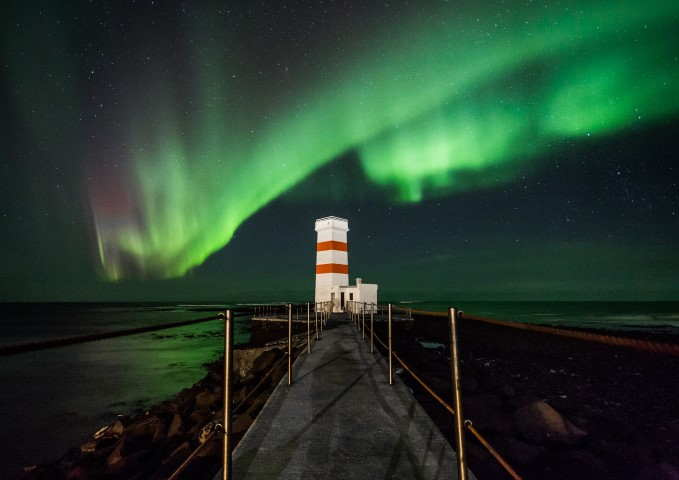 Aurora Borealis dancing over a lighthouse in Iceland