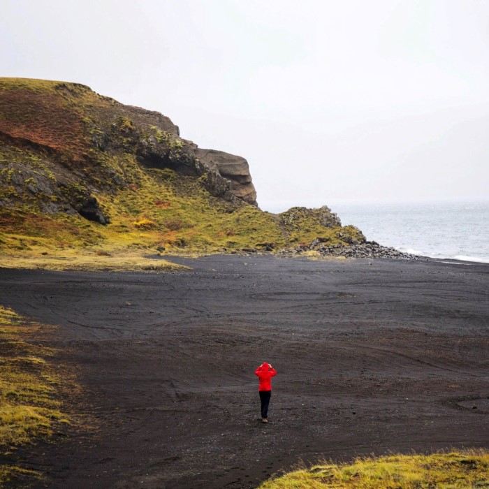 Woman walking over black sand beach