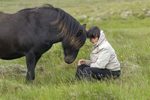 A woman and a horse sharing a moment