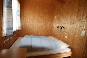 The bedroom of the three person cottage has a bunk bed and a double bed