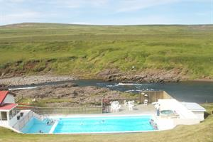 The swimming pool at Selárdalur is located next to a beautiful salmon river